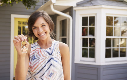 Young woman holding the keys to her new home
